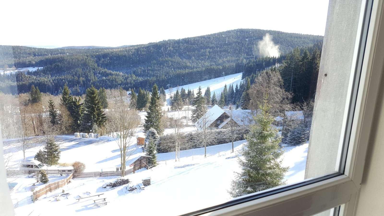 Výhled na skiareál Zadov z pokoje hotelu Zadov v zimě